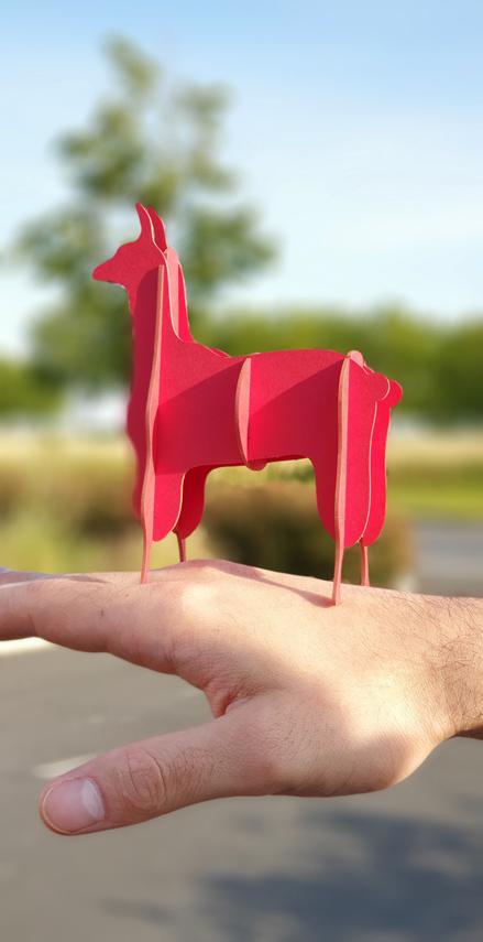 Lama rouge en carton compact sur main par Nonitt Paper Sculptures