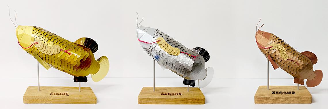 3 trophées sculpture poisson Arowanas en papier or, argent et cuivre